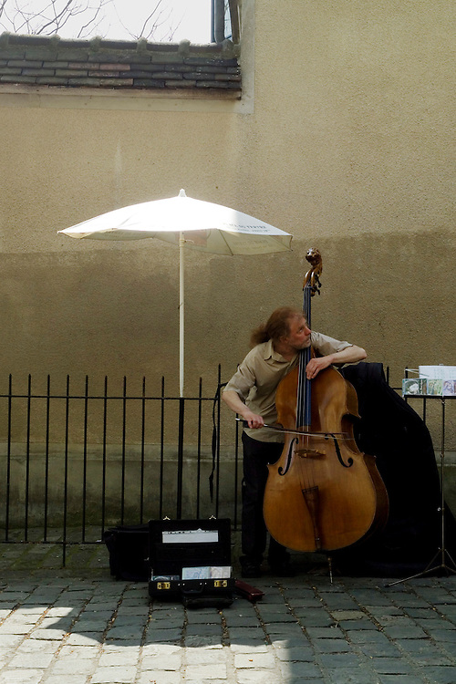 Male street player with red hair in a ponytail making music on his acoustic bass on a brick paved street in  Montmartre Paris, France near Sacre Coeur. A small tip case with a sign on the lid sits on the sidwalk.