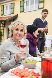 Senior woman smiling with wine glass and enjoying outdoor party with her family and friends at farmhouse, Bavaria, Germany