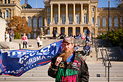 """07 NOVEMBER 2020 - DES MOINES, IOWA: A man carries a Trump 2020 flag at the Iowa State Capitol during a """"Stop the Steal"""" rally Saturday. They were protesting the ongoing efforts to count the votes in states like Arizona and Nevada. There were rival election rallies at the State Capitol in Des Moines Saturday. About 1,000 supporters of President Donald Trump gathered on the steps of the State Capitol and called for an end to vote counting. About 300 supporters of President Elect Joe Biden gathered in People's Plaza, on the south lawn of the Capitol, and called for the vote count to continue until every vote was counted.     PHOTO BY JACK KURTZ"""