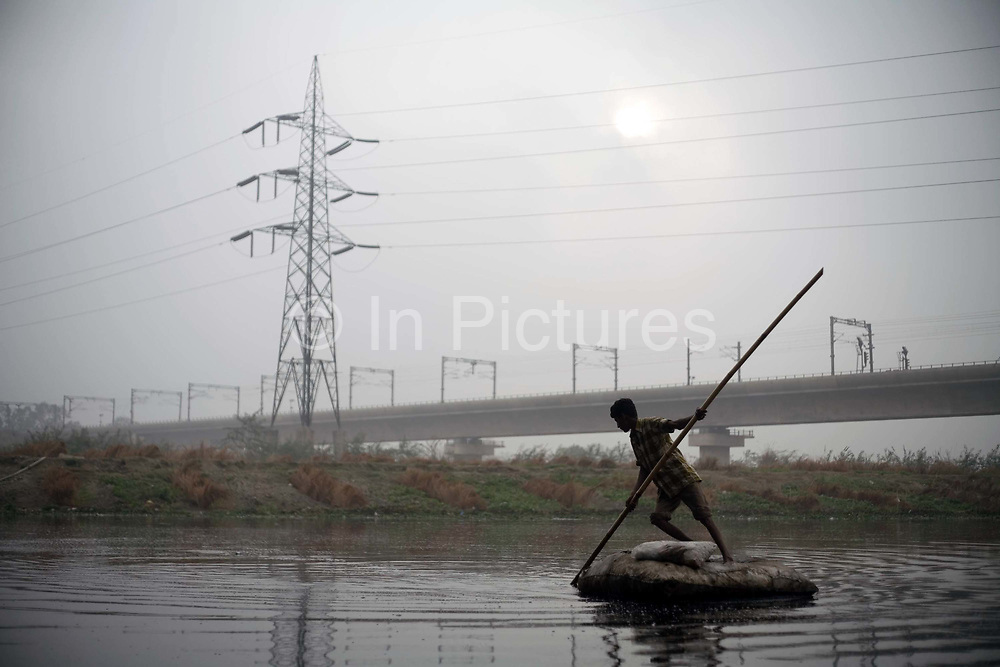 A scavenger looks for discarded waste to sell on a home made raft of rags in the Yamuna River by the Kudsia Ghat in Delhi. The river is so polluted it can no longer support life yet a community live and work on it's banks. This boy uses a powerful magnet to dredge for coins and other metals which he can sell.