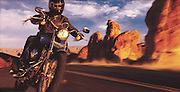 A man rides his motorcyle along a desert road in Arizona