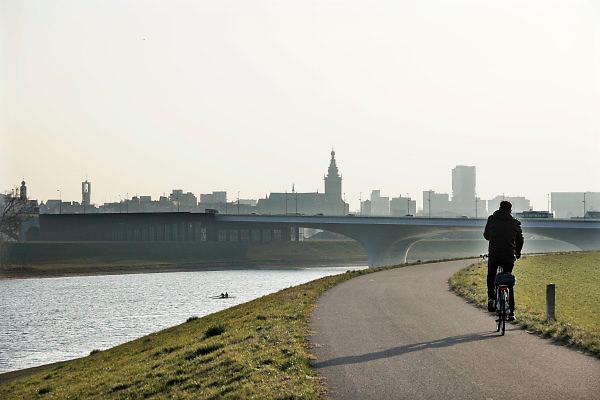 Nederland, Nijmegen, 21-2-2018De Nevengeul in de Waal en de verlengde waalbrug, een van de grotere waterwerken om de waterstanden in de nederlandse rivieren bij hoogwater omlaag te krijgen . een fietser fietst op de dijk .Foto: Flip Franssen