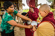 25 MAY 2013 - MAE SOT, TAK, THAILAND: A Roman Catholic Burmese woman of Indian ancestry gives food to Burmese Buddhist novices in an unofficial village of Burmese refugees north of Mae Sot, Thailand. They live on a narrow strip of land about 200 meters deep and 400 meters long that juts into Thailand. The land is technically Burma but it is on the Thai side of the Moei River, which marks most of the border in this part of Thailand. The refugees, a mix of Buddhists and Christians, settled on the land years ago to avoid strife in Myanmar (Burma). For all practical purposes they live in Thailand. They shop in Thai markets and see their produce to Thai buyers. About 200 people live in thatched huts spread throughout the community. They're close enough to Mae Sot that some can work in town and Burmese merchants from Mae Sot come out to their village to do business with them.   PHOTO BY JACK KURTZ