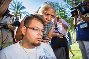 25 JUNE 2012 - PHOENIX, AZ: JOSE LUIS LEAL, left, and PETRA FALCONE, both from Promise AZ, (PAZ) read the US Supreme Court's ruling on SB 1070 at the Arizona State Capitol in Phoenix, AZ, Monday after the court ruled on a lawsuit brought against Arizona by the Obama administration. The lawsuit, US v. Arizona, determines whether or not Arizona's tough anti-immigration law, popularly known as SB1070 is constitutional. Among other things, the law requires police officers to check the immigration status of anyone whom they arrest, allows police to stop and arrest anyone whom they believe to be an illegal immigrant, makes it a crime for someone to be in the state without valid immigration papers, and makes it a crime to apply for or hold a job in Arizona without proper papers. The federal government sued Arizona because it believes the law is invalid because it is trumped by federal immigration laws. The court struck down most of the law but left one section standing, the section authorizing local police agencies to check the immigration status of people they come into contact with.    PHOTO BY JACK KURTZ