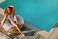 Woman Relaxing by Swimming Pool, High Angle View