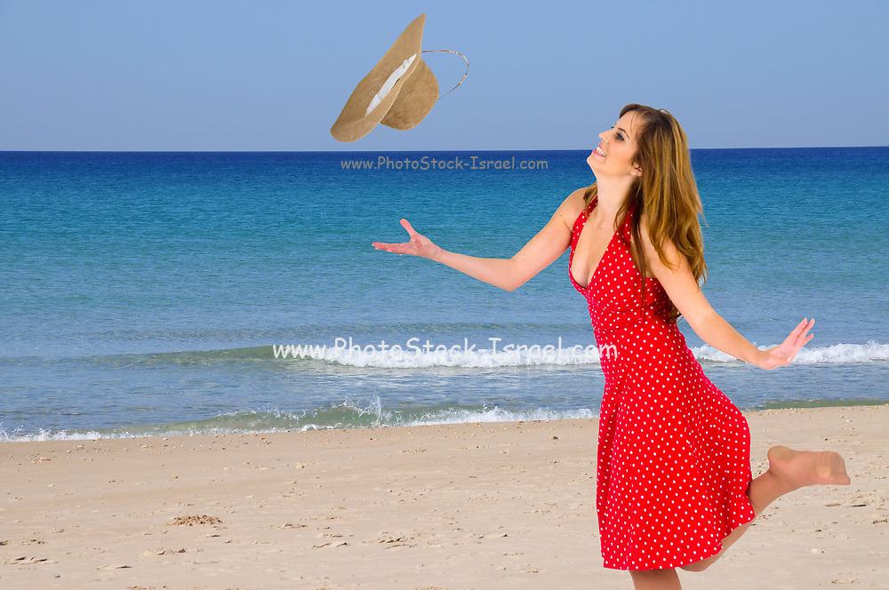 Young woman in summer dress and straw hat on the beach