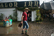 A man walks through deep mud in the sun with his good shoes in his hands at the Glastonbury Festival 22th July 2016, Somerset, United Kingdom.  The Glastonbury Festival runs over 3 days and has 3000 acts, including music, art and performance and approx. 150.000 attend the anual event.