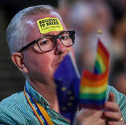 © Licensed to London News Pictures. 18/09/2018. Brighton, UK.  A party delegate waves the EU flag and an LGBT rainbow flag while listening to a debate at the final day of the Liberal Democrat Autumn Conference in Brighton, East Sussex on September 18, 2018. This years event has been mainly focused around Brexit, the UK's departure from the EU. Photo credit: Ben Cawthra/LNP