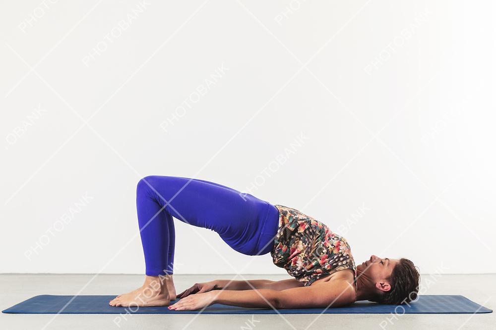 woman in the position of bridge pose in studio