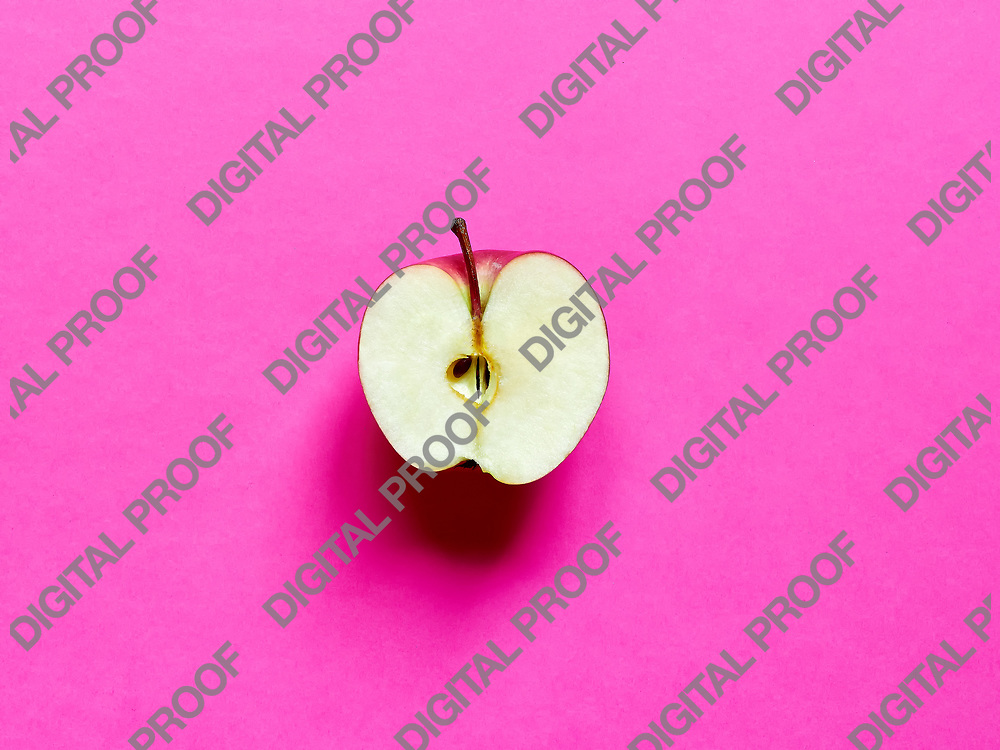 Apple fruit sliced by half isolated in studio over a fucsia pink background