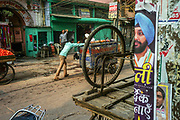 A vendor pushes his cart past a political poster on the street in Sitaram Bazar, Old Delhi, India.