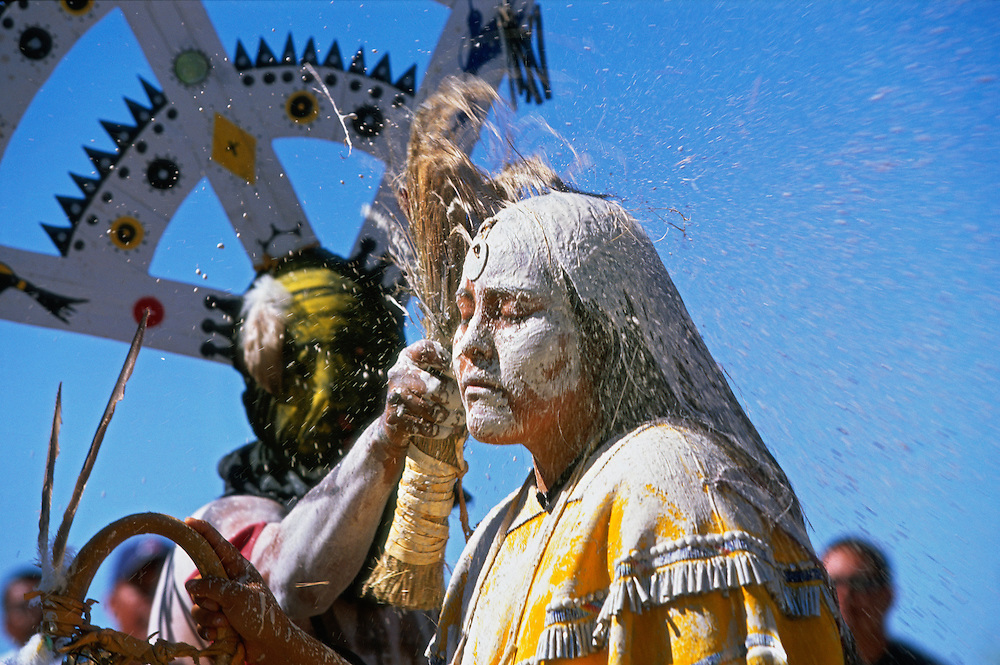 An Apache girl is painted white with sacred clay and corn meal during her Sunrise Dance, a first menstruation rite, the San Carlos Apache Reservation, Arizona, USA. She is painted by a Mountain Spirit or Crown Dancer, and the staff in her hand symbolises longevity. The painting of the girl is both a blessing and an enactment of certain parts of the Apache creation myth. During the rites the girl becomes Changing Woman, a mythical female figure, and comes into possession of her healing powers. The rites are also supposed to prepare the girl for adulthood and to give her a long and healthy life without material wants.