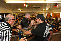 Badger Drewes and Ronnie Bean officiate a match with Travis Josselyn and Corey Dupuis during the Arm Wrestling Tournament to benefit the Fallen 7 at the Laconia VFW on Saturday.  (Karen Bobotas/for the Laconia Daily Sun)