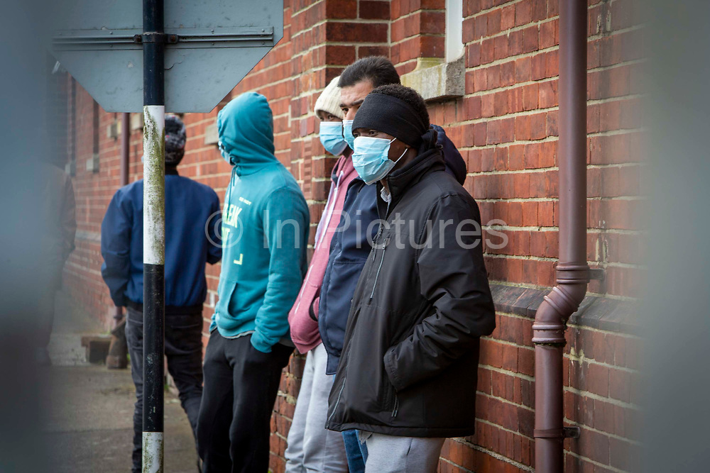 Asylum seekers stand behind fencing wearing mask inside Napier Barracks on the 12th of January 2021, Folkestone, United Kingdom. Over 400 asylum seekers are being kept at Napier Barracks in unsuitable, cold accommodation, they are experiencing mental health issues as well as being vulnerable to health conditions including COVID-19. 3 people living inside the barracks have attempted suicide in 2021 already.