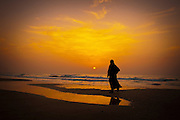Silhouette of a woman on a Mediterranean beach at sunset