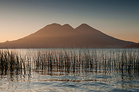 Sunrise paints the volcanic peaks above Lake Atitlan in the highlands of Guatemala.