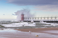 A seagull perched on a child's sandal watches on as a wave engulfs the South Haven Lighthouse on an early Autumn morning
