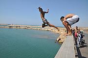 Israel, Tel Aviv Youth jump into the Yarkon river from a pedestrian bridge