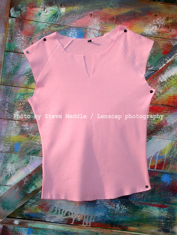 Ladies Pink T Shirt on a Graffiti Covered Wooden Fence.