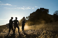 Leadership from Echo Company chat as the sun goes down behind them during live-fire exercises for the 2nd Battalion, 5th Marine Regiment at Camp Pendleton.