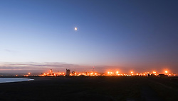 © Licensed to London News Pictures. <br /> 16/01/2015. <br /> <br /> South Gare, United Kingdom<br /> <br /> The lights of industrial Teesside shine at first light on a clear morning. Further bad weather is expected to sweep across the country through the day.<br /> <br /> Photo credit : Ian Forsyth/LNP