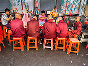 03 NOVEMBER 2014 - YANGON, MYANMAR:  Burmese Buddhist novices eat breakfast at a street food stand in Yangon. Most young males in Myanmar (Burma) go into the monastery and become monks, some for only a few months, others for longer periods.    PHOTO BY JACK KURTZ