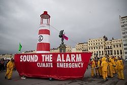 """© Licensed to London News Pictures . 22/09/2019. Brighton, UK. The words """" Sound the alarm climate emergency """" written on the side of the lighthouse boat . Environmental campaigners from Extinction Rebellion highlight the climate emergency and deploy a large red and white lighthouse lightship named """" Greta """" , on Brighton Promenade , during the second day of the 2019 Labour Party Conference from the Brighton Centre . Photo credit: Joel Goodman/LNP"""