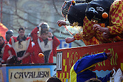 Members of the Chess (one of the groups fighting from a horse-van, and symbolising the guards of Count Ranieri) are engaged in an open fight during The Battle of the Oranges in Freguglia Square, Ivrea, pop. 30.000. During the days of the Carnival, the town becomes crammed with tourists coming to witness the event which finds its roots at the end of the XII Century, when the people led an insurrection against the local tyrant, Count Ranieri of Biandrate, who was exercising the 'jus primae noctis' rule (having the first night) on the local young brides. The battle to overthrow him is represented with a 3-day-fight between factions in which more then 400 tonnes of oranges are thrown. During the celebrations, food stalls, bands playing music, and parades are also present, giving it a typical Medieval atmosphere. .