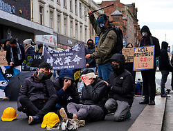 Glasgow, Scotland, UK. 19 January, 2020. Hong Kong students and Amnesty International stage a pro-democracy protest on Sauchiehall Street in Glasgow city centre. The protest was one of several in cities worldwide to protest against the anti-democratic policies of the Chinese Communist Party. Pictured. Protestors act out scenes from Hong Kong showing alleged police brutality towards protestors.  Iain Masterton/Alamy Live News.
