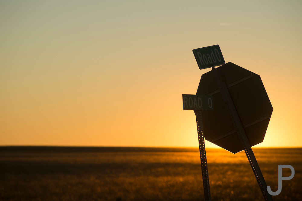 The sun rises behind a stop sign at Road 0 in the Oklahoma panhandle.