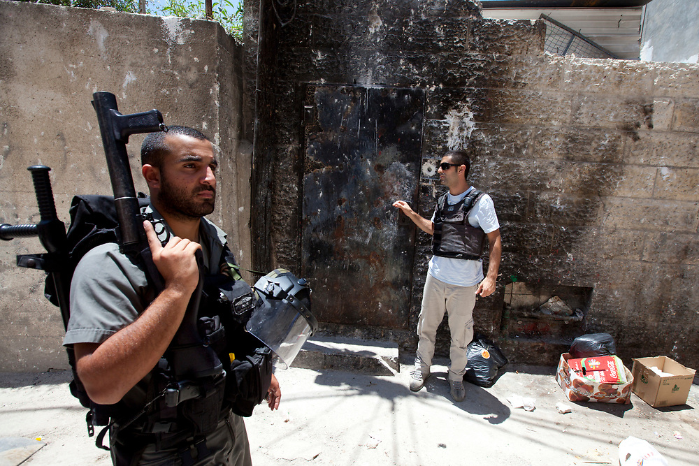An Israeli border policeman patrols near the entrance to a Jewish house in the east Jerusalem neighborhood of Silwan, during a visit by the Israeli parliament committee for the children's rights to houses of Jewish families residing in a mostly Palestinian area, on July 6, 2010.