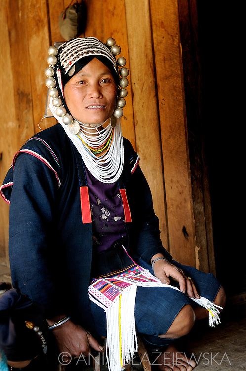 Burma/Myanmar. Akha woman sitting on the terrace of her house.