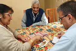 Son helping elderly south Asian parents with budgeting.