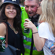 A Metropolitan police officer with love hearts painted on his cheeks gets a kiss. A young woman wears his bobby helmet after he let her borrow it for a kiss. The Notting Hill Carnival has been running since 1966 and is every year attended by up to a million people. The carnival is a mix of amazing dance parades and street parties with a distinct Caribbean feel.