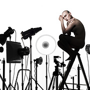 A female model perched on a stepladder above a sea of lights in a photography studio.