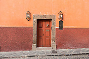 Spanish colonial style homes and old wooden door along Hospicio Street in the historic center in San Miguel de Allende, Mexico.