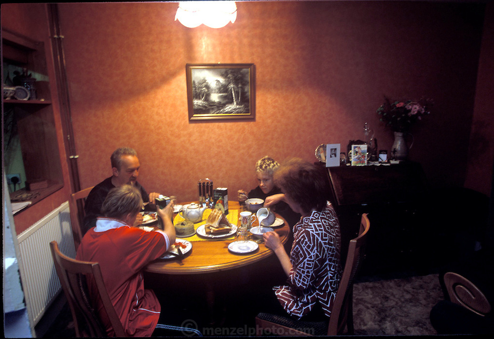 (MODEL RELEASED IMAGE). The Baintons, who call themselves the Bees, enjoy a family breakfast at home. Mark cooks breakfast; a task he performs every weekend morning, unless, of course, he can persuade his wife Deb to do it. (Supporting image from the project Hungry Planet: What the World Eats.) The Bainton family of Collingbourne Ducis, Wiltshire, England, is one of the thirty families featured, with a weeks' worth of food, in the book Hungry Planet: What the World Eats.