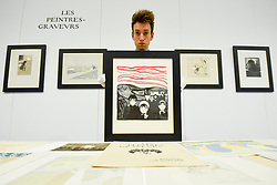 """© Licensed to London News Pictures. 12/09/2019. LONDON, UK.  A technician presents a lithograph by Edvard Munch at a photocall for """"Les Peintres-Graveurs"""", a multi-artist portfolio of lithographs published in 1896 by Ambroise Vollard, to be auctioned at Sotheby's on September 17 with an estimate of £500,000 to £1,000,000.  It is the only known complete example and includes 22 prints by the greatest Impressionist and Post-Impressionist artists such as Pierre Bonnard, Odilon Redon, Théo van Rysselberghe, Auguste Renoir, and Edouard Vuillard., as well as the first colour lithograph by a then not so well-known Edvard Munch.  Photo credit: Stephen Chung/LNP"""