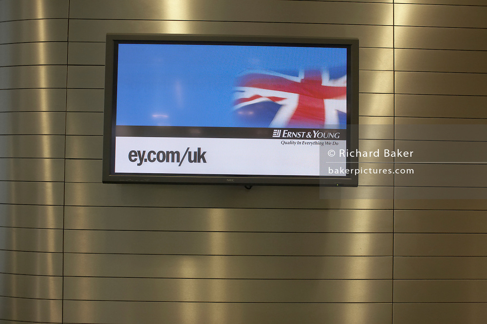 TV screen displaying corporate logo greeting message at main entrance of auditing company Ernst & Young's London headquarters