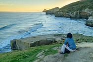 Oceania, New Zealand, Aotearoa, South Island, Otago Coast, Dunedin, Tunnel Beach, woman watching waves