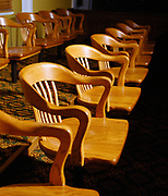 Dramatic lighting on classic wooden jury box chairs in a courthouse