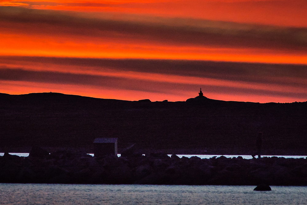 A sunset very colorful this fall. We dont see that very often. Fall time is very cloudy in Inukjuak. If you look well, you will see the monument I remember on the top of the hill.