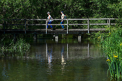 © Licensed to London News Pictures. 21/05/2020. CHORLEYWOOD, UK.  People cross the River Chess near Chorleywood, Hertfordshire during warm weather where temperatures are forecast to rise to 26C.  Enjoying the outdoors for many has been a welcome relief as the UK government has slightly eased coronavirus pandemic lockdown restrictions which allows for unlimited daily exercise as long as social distancing is maintained.  Photo credit: Stephen Chung/LNP