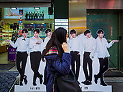 "14 OCTOBER 2018 - SEOUL, SOUTH KOREA: A woman walks past a cardboard figure of the K-Pop boy band ""BTS"" in front of a cosmetics shop in the neighborhood around Myeongdong Street between the Cathedral and City Hall in Seoul. It's a high end shopping, dining and entertainment district, popular with tourists and wealthy South Koreans.      PHOTO BY JACK KURTZ"
