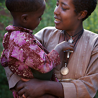 """Wubalem and her daughter Rekebki in the village of Mecha.<br /> <br /> Wubalem Shiferaw, age 23, lives in the village of Mecha with her husband Tsega Bekele, age 33, and their daughter Rekebki, age 4. Wubalem remembers her grandparents harvesting honey. She has maintained this tradition while moving to modern hives which produce a far greater yield of honey. Wubalem is a member of the Mecha village Cooperative which brings together local women beekeepers allowing them to share insights and build a credit union. The Mecha village Cooperative is not yet a member of the Zembaba Union. Wubalem's husband Tsega is a priest and a tailor. <br /> <br /> Harvesting honey supplements the income of small farmers in the Ethiopian region of Amhara where there is a long tradition of honey production. However, without the resources to properly invest in production and the continued use of of traditional, low-yielding hives, farmers have not been able to reap proper reward for their labour. <br /> <br /> The formation of the Zembaba Bee Products Development and Marketing Cooperative Union is an attempt to realize the potential of honey production in Amhara and ensure that the benefits reach small producers. <br /> <br /> By providing modern, high-yield hives, protective equipment and training to beekeepers, the Cooperative Union helps increase production and secure a steady supply of honey for which there is growing demand both in and beyond Ethiopia. The collective processing, marketing and distribution of Zembaba's """"Amar"""" honey means that profits stay within the cooperative network of 3,500 beekeepers rather than being passed onto brokers and agents. The Union has signed an agreement with the multinational Ambrosia group to supply honey to the export market. <br /> <br /> Zembaba Bee Products Development and Marketing Cooperative Union also provides credit to individual members and trains carpenters in the production of modern hives. <br /> <br /> Photo: Tom Pietrasik<br /> Mecha,"""