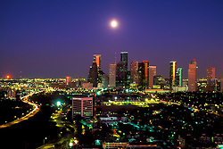 Aerial view of Houston, Texas skyline and city lights at night with glowing moon.
