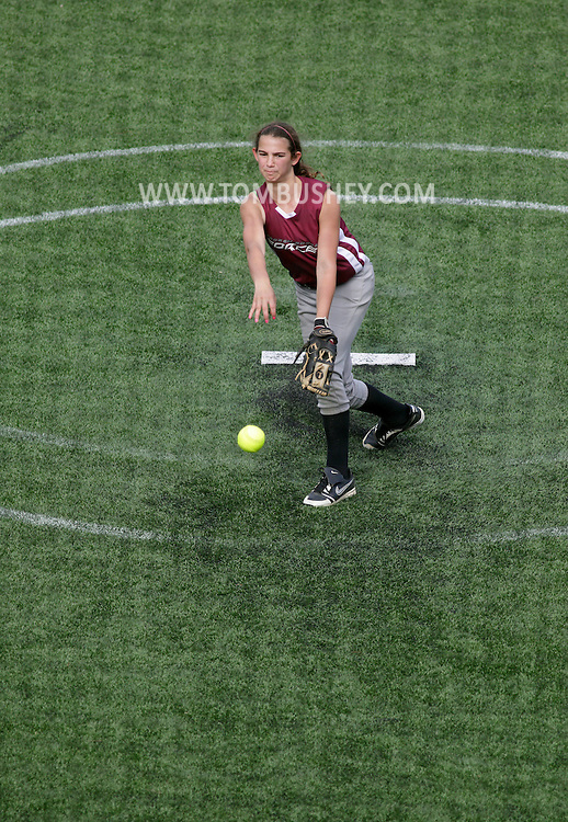 Chester, New York - A girl pitches the ball during a youth softball tournament at the Rock Sports Park on May 21, 2011. The image was shot through the black netting behind home plate.