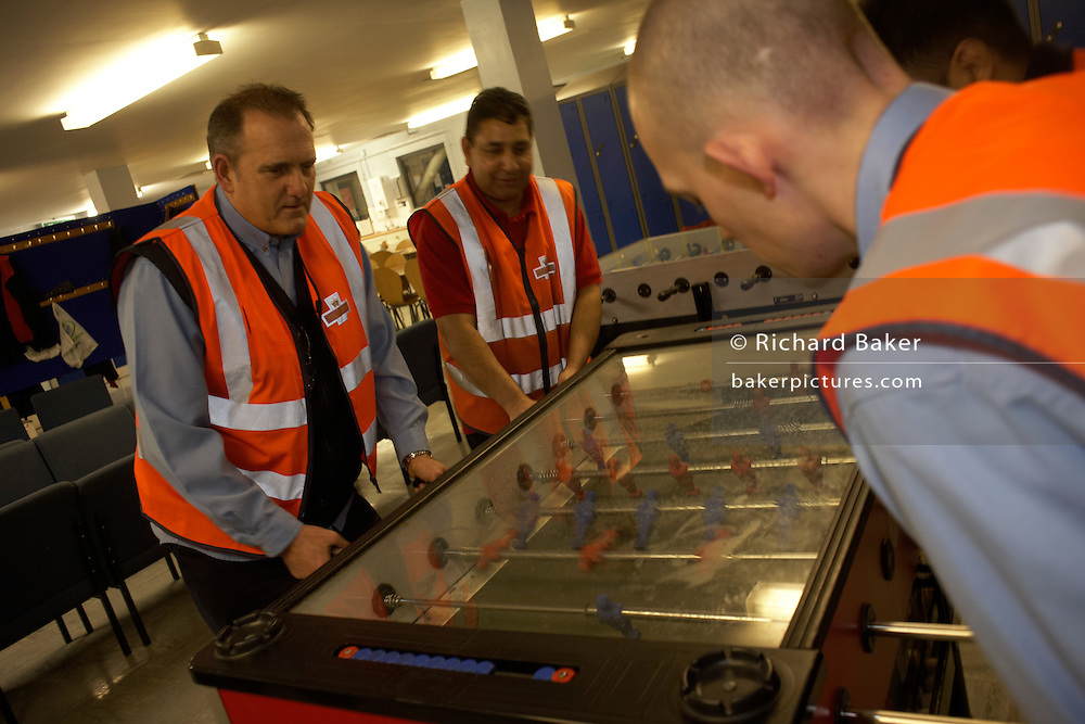 Postal workers play table football in the canteen during a night shift at Royal Mail's DIRFT logistics park in Daventry