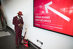 © Licensed to London News Pictures . 25/09/2016 . Liverpool , UK.  A man wearing a red hat and a maroon suit charges his phone on a wall socket at the ACC in Liverpool Docks , during the first day of the Labour Party Conference . Photo credit : Joel Goodman/LNP