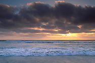 Coastal fog at sunset moving in over the ocean as waves break in suf, Torrey Pines State Beach, San Diego, California